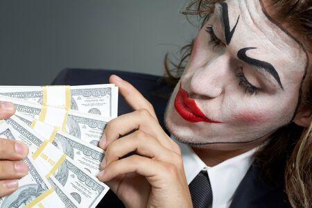cara pintada: Retrato de hombre con la cara pintada contando billetes Foto de archivo