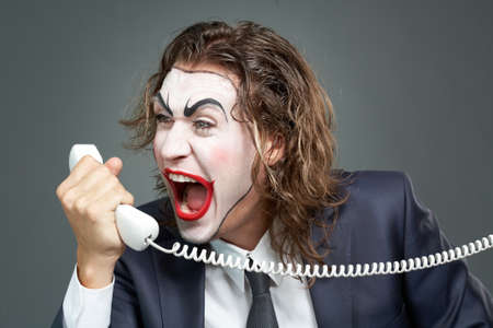 Portrait of businessman with painted face shouting at telephone receiver Stock Photo - 9963238