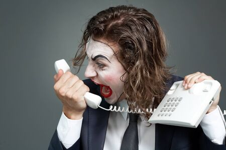 Portrait of businessman with theatrical makeup shouting at telephone receiver Stock Photo - 9963155