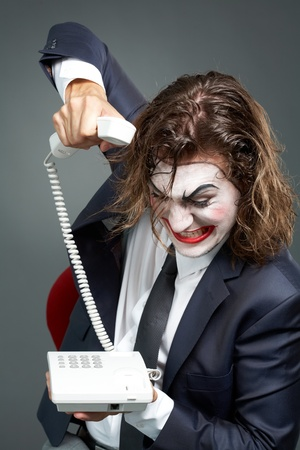 Portrait of furious businessman with theatrical makeup ringing off photo