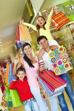 ni�os de compras: Padres con dos hijos tiendas en el centro de comercio Foto de archivo
