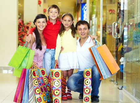 malls: Portrait of a nice family of four with shopping bags looking at camera and smiling Stock Photo