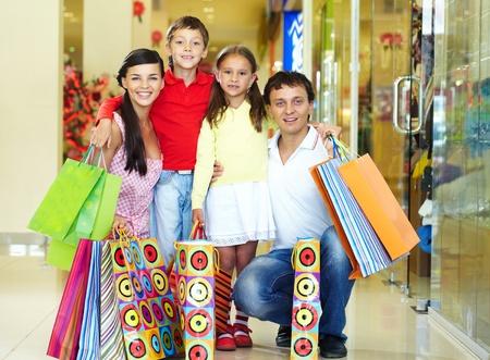 ni�os de compras: Retrato de una familia de cuatro con bolsas de compras, mirando a la c�mara y sonriente Niza