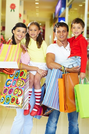 happy family shopping: Portrait of couple with two children and shopping bags looking at camera and smiling