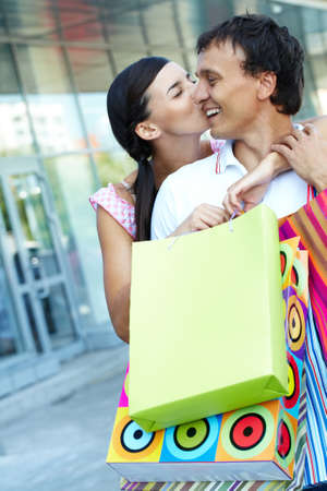 Young girl kissing her boyfriend with shopping bags photo