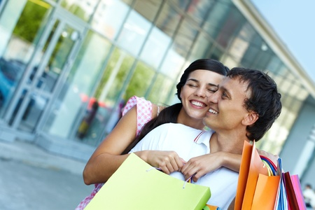 Young girl embracing her boyfriend with shopping bags photo