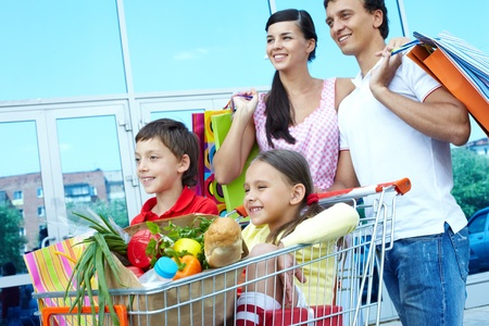 Couple with shopping bags pushing cart with two children photo