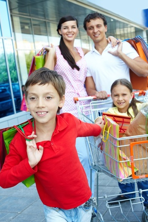 Little boy with sister and parents with shopping bags behind  Stock Photo - 9963250