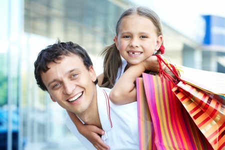Portrait of father with daughter and shopping bags on back  photo