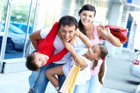 ni�os de compras: Retrato de familia feliz de cuatro con bolsas de compras
