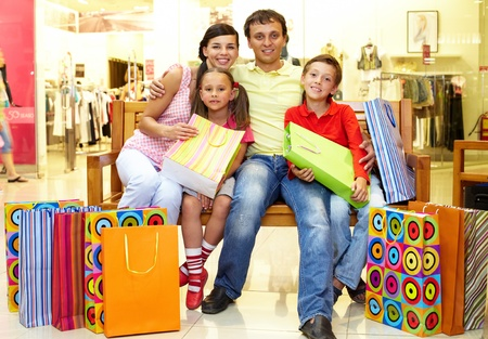 Portrait of a family sitting on bench in store with plenty of shopping bags photo