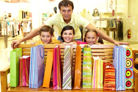 Portrait of a family at bench with plenty of shopping bags looking at camera and smiling  photo
