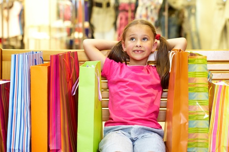 A little girl sitting on bench with plenty of shopping bags photo