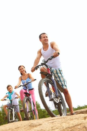 Family with one child cycling together Stock Photo