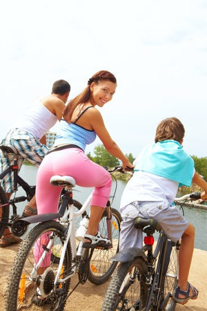 Rear view of family of three on bikes photo