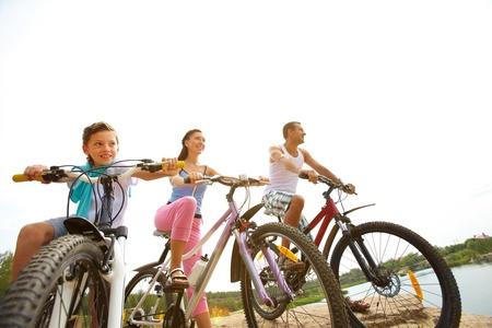 family bike: Family of three sitting on bikes Stock Photo