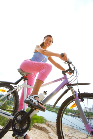 bicyclists: Portrait of young woman riding bicycle Stock Photo