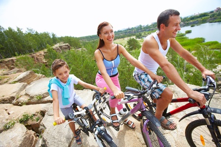 Portrait of family of three with bikes on a rock  photo