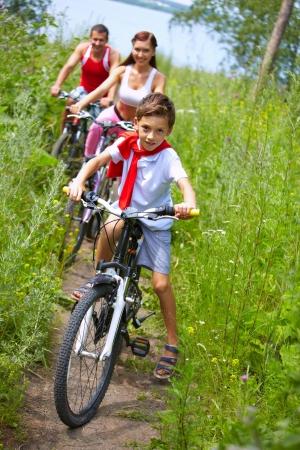riding bike: Ragazzino in bicicletta con i suoi genitori