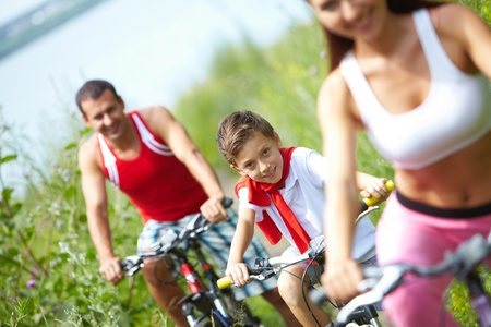 A little boy sitting on bike between mother and father  photo