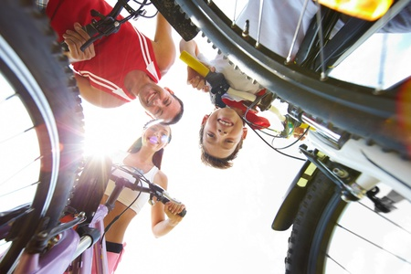 Below view of family of three on bikes looking at camera photo