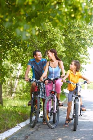 ni�os en bicicleta: Retrato de familia de tres ciclos en madera Foto de archivo