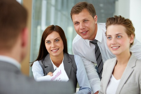 Two happy managers looking at business partner at meeting photo