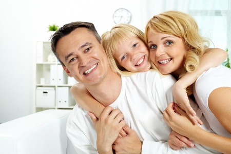 Portrait of happy parents with their daughter looking at camera at home Stock Photo - 10068490