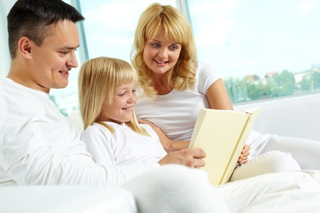 Image of friendly family sitting on the sofa and reading book   photo