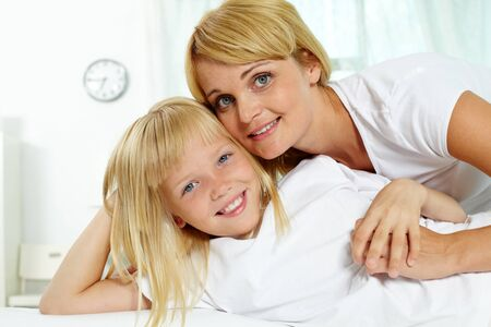 Portrait of happy mother embracing daughter and both looking at camera Stock Photo - 10068572