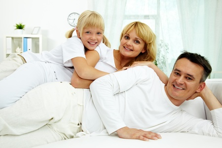 Portrait of happy parents with their daughter having rest at home  photo