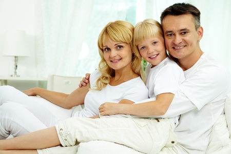 Portrait of happy parents and their daughter looking at camera with smiles  photo