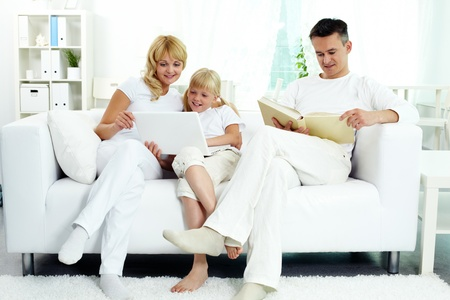 family sofa: Image of family sitting on the sofa and spending free time at home