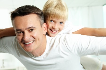Portrait of happy father holding daughter on back and both looking at camera Stock Photo - 10068520