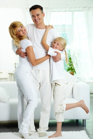 Portrait of happy parents and their daughter looking at camera with smiles  Stock Photo
