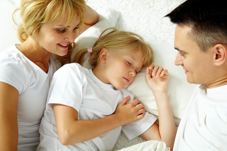 sleeping kid: Portrait of calm girl sleeping while parents looking at her
