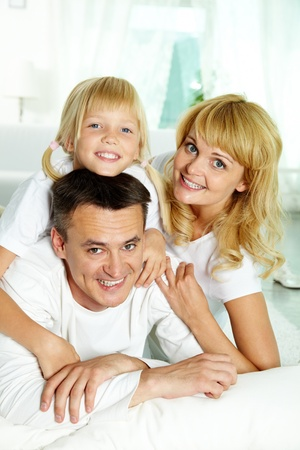 Portrait of happy parents with their daughter looking at camera at home Stock Photo - 10068502