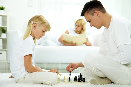 jugando ajedrez: Imagen de padre e hija jugando al ajedrez en casa