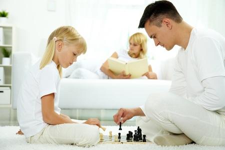 frau sitzt am boden: Vater und Tochter spielt Schach zu Hause   Lizenzfreie Bilder