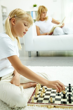 Image of intelligent girl playing chess with somebody   photo