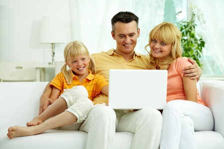 man using computer: Image of friendly family sitting on the sofa and looking at laptop