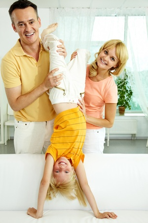 Portrait of happy parents playing with their daughter at home  Stock Photo - 10068518