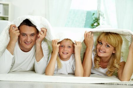Portrait of happy parents and their daughter with blanket above their heads Stock Photo - 10068407