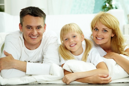Portrait of happy parents and their daughter looking at camera at home  photo