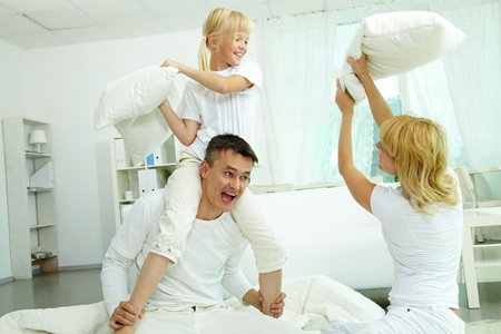 pillow fight: Portrait of happy parents and their daughter having fun at home  Stock Photo