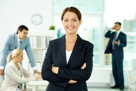Een mooie zakenvrouw op zoek naar camera met werkende mensen op achtergrond