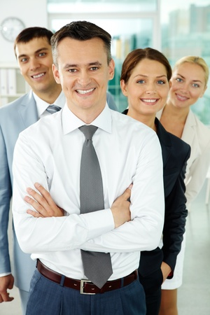 Portrait of business partners looking at camera with their leader in front photo