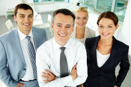 methods: Portrait of business partners looking at camera with their leader in front