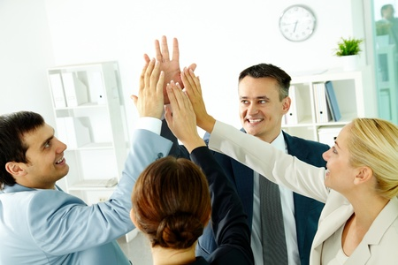 Portrait of business group keeping hands close to each other meaning support photo