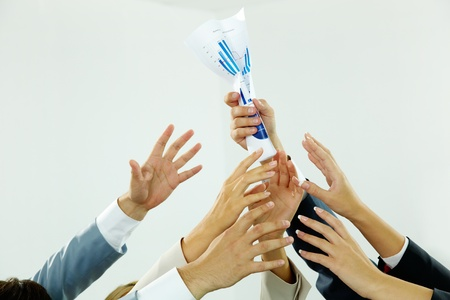 business rival: Image of several human hands trying to get paper from male hand Stock Photo